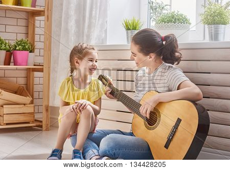 Happy family. Mother and daughter playing guitar together. Adult woman playing guitar for child girl.