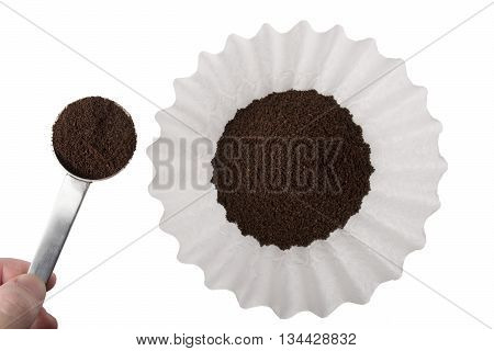 Ground coffee being scooped into a white basket style coffee filter isolated on white.