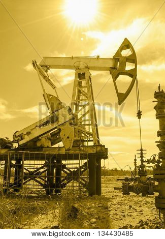 Pump jack and wellhead in the oilfield. Oil and gas concept. Toned.