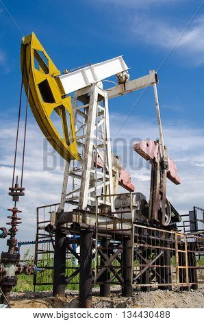 Pump jack and wellhead in the oilfield. Oil and gas concept.