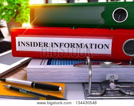 Red Ring Binder with Inscription Insider Information on Background of Working Table with Office Supplies and Laptop. Insider Information Business Concept on Blurred Background. 3D Render.