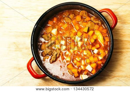 Meat stew with vegetables in red pot on wooden table background