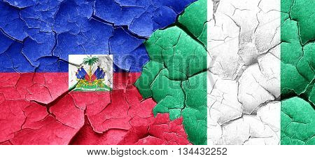 Haiti flag with Nigeria flag on a grunge cracked wall