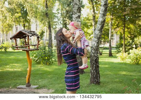 Woman is holding and kissing baby girl outdoors dressed in stripped dresses. Happy family. Happy childhood. Maternity.