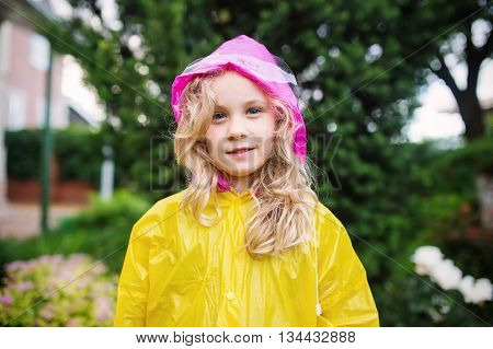 Outdoor photo of little blonde girl in yellow raincoat.