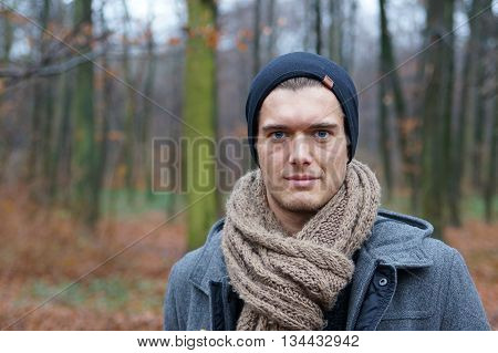 young man with scarf and woolly hat in autumn winter landscape