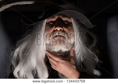 Druid old man with long grey hair and beard in hunter hat with bird feathers face illuminated on dark background