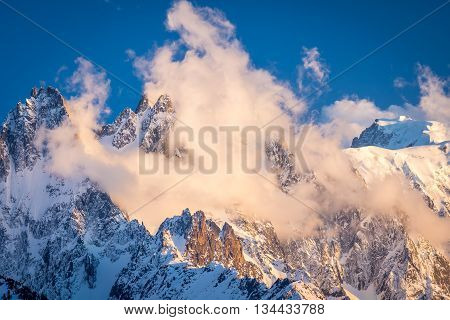 Alpenglow and clouds over Chamonix Aiguilles, French Alps