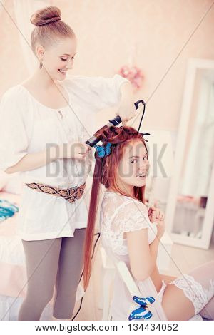 Hair stylist makes the bride before the wedding