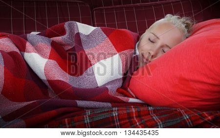 young woman slip on sofa on red pillow covered by red checkered blank horizontal close up