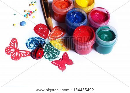 Set of gouache paints with brush in palette and flower picture on white background closeup