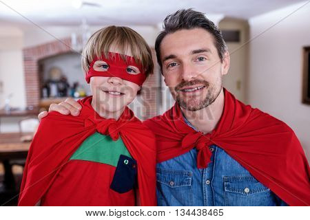 Portrait of father and son pretending to be superhero in living room at home