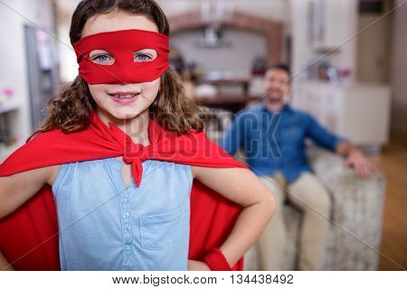 Daughter pretending to be a superhero while father sitting on sofa at home