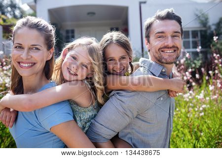 Portrait of parents giving a piggy back to their daughters in the garden