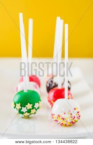 Sweet colorful cake pops on yellow background