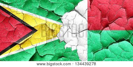 Guyana flag with Madagascar flag on a grunge cracked wall