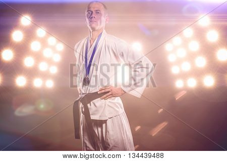 Fighter posing with medal around his neck against digitally generated image of spotlight