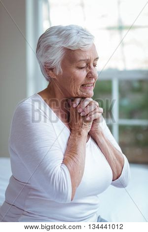 Senior woman praying at home against window at home