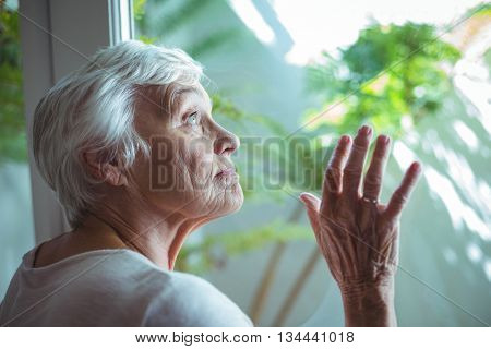 Thoughtful senior woman looking through house window at home