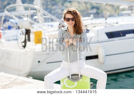 Cute young woman with gray eyes, curly red hair and a sweet smile, dressed in white trousers and a light shirt with stripes, sitting alone on the pier near the yacht club, with a light-green suitcase with wheels on a background of yachts and boats near th
