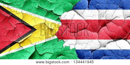 Guyana flag with Costa Rica flag on a grunge cracked wall