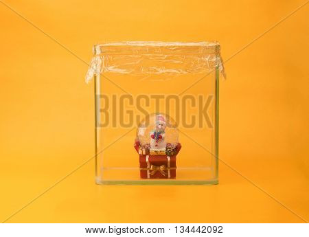 Global warming, green house gas,  Climate change, Rising temperature concept image. Snow man snow dome in a glass aquarium with plastic wrap lid.