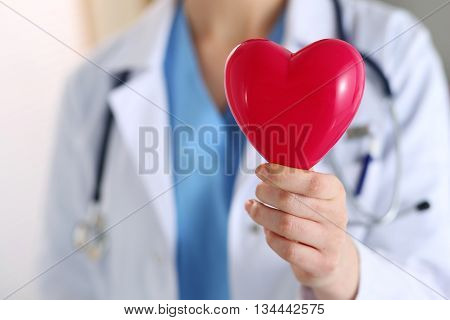 Female medicine doctor hands holding red toy heart in front of her chest closeup. Medical help cardiology care health prophylaxis prevention insurance surgery and resuscitation concept