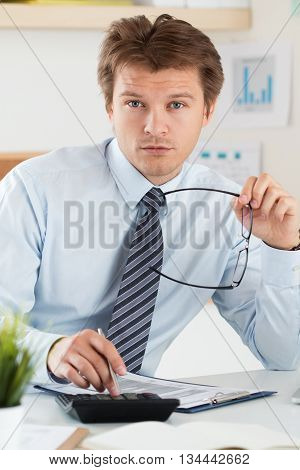 Portrait of bookkeeper or financial inspector holding his glasses making report calculating or checking balance. Home finances investment economy saving money or insurance concept