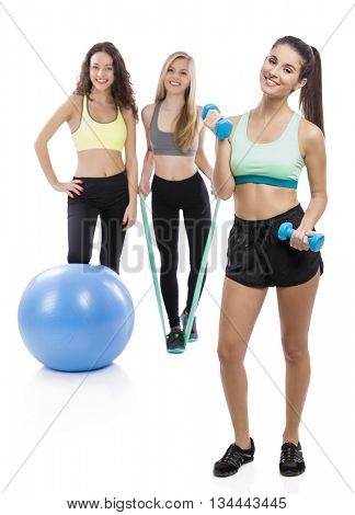 Portrait of three beautiful athletic girls in the gym