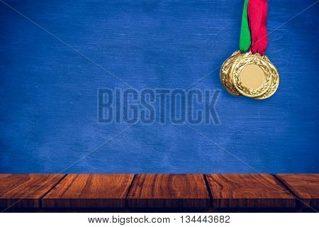 Composite image of gold medals against white background with vignette