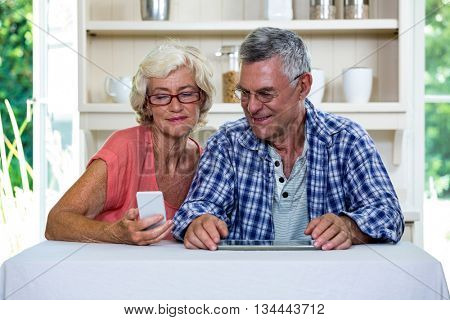 Senior couple using mobile phone in kitchen at home