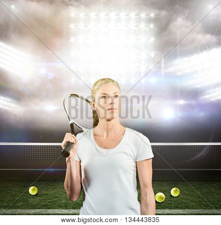 Female tennis player posing with racket against american football arena