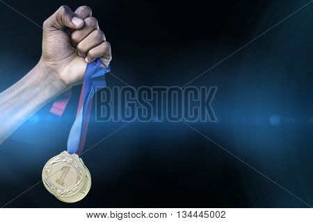 Hand holding two gold medals on white background against spotlights