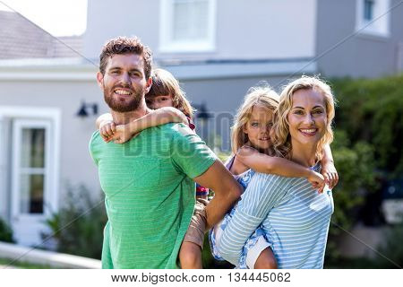 Portrait of cheerful parents piggy-backing children against house
