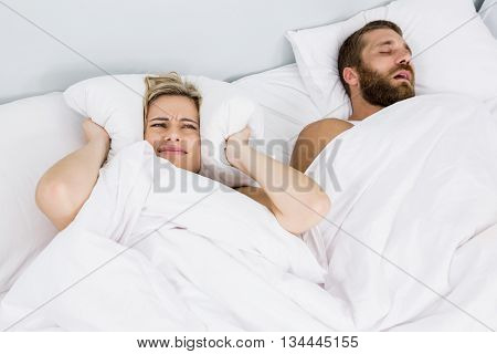 Woman covering ears while man snoring on bed at home