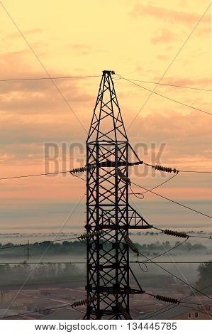 Electricity pylon on sunset sky background taken closeup.