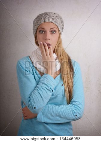 shocked young woman wearing wool cap indoors