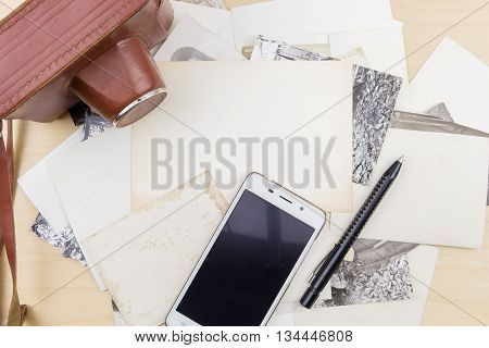 Old Camera And Smartphone On Stack Of Photos, On Wooden Surface.