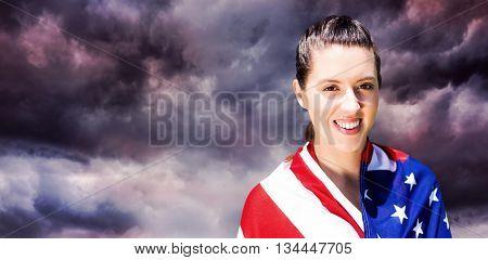 Portrait of happy american sportswoman smiling against gloomy sky