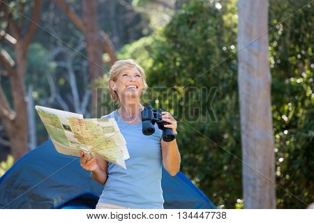 Mature woman smiling and holding binoculars and map on camp site