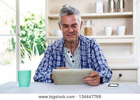 Senior man using digital tablet against shelves in kitchen