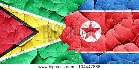 Guyana flag with North Korea flag on a grunge cracked wall