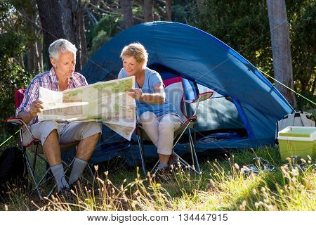 Mature couple looking map on their camp site on the wood