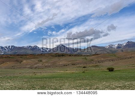 The picturesque steppe desert landscape with mountains and the dry ground with sparse vegetation on a background of blue sky and clouds