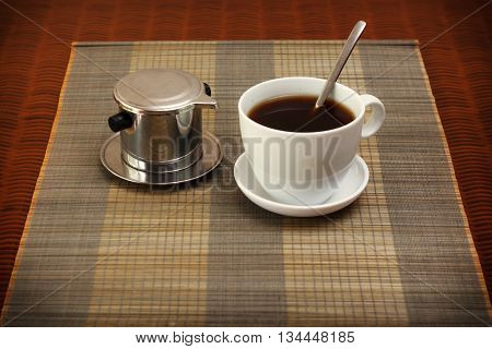 Morning coffee served in vietnam coffee filter on rattan table natural light photo closeup horizontal view