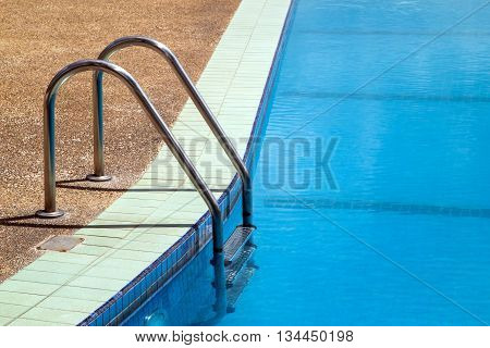 Outdoor swimming pool with handrail and access ladder
