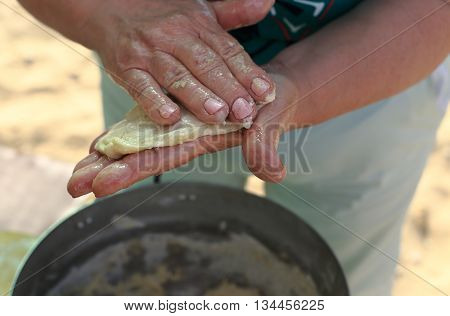 woman's hand close-up. dough in his hands and does pizza. in the pan is big dough