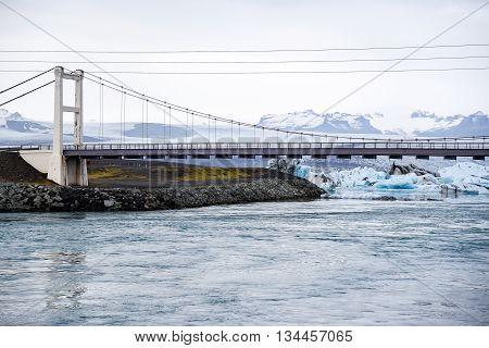 The bridge near blue Icebergs in Jokulsarlon glacier lagoon famous natural landmark of Iceland