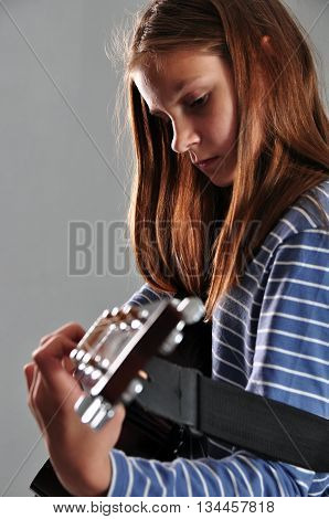 Pretty young teen girl playing acoustic guitar