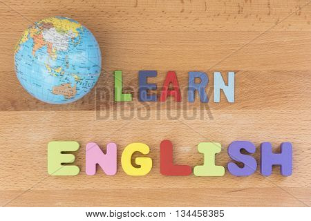 word learn english with globe over wooden background education concept top view